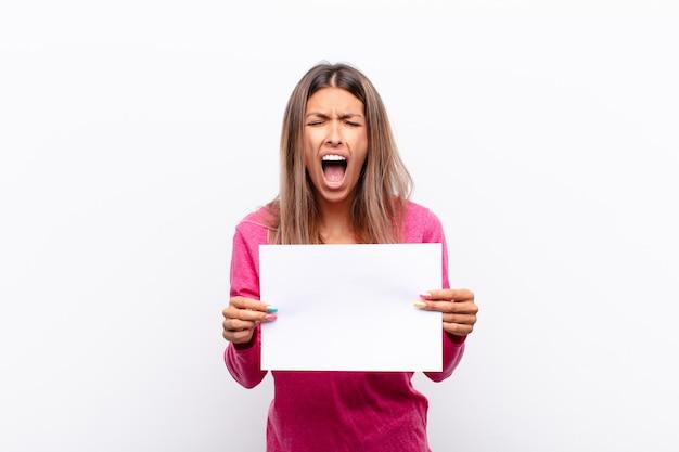 Молодая симпатичная женщина, кричащая агрессивно, выглядит очень злой, расстроенной, возмущенной или раздраженной, крича не держащей плакат