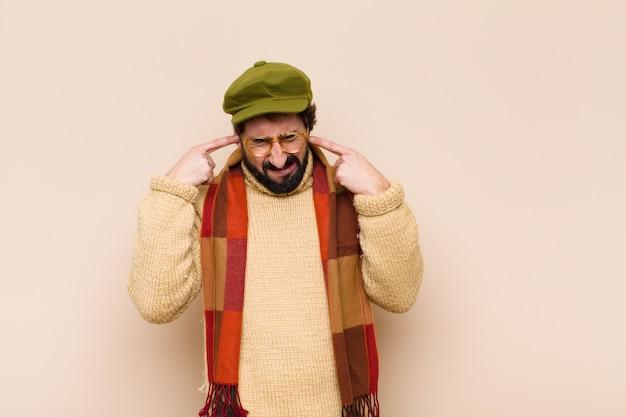 Молодой спокойный бородатый мужчина выглядит злым, напряженным и раздраженным, закрывая оба уха оглушительным шумом, звуком или громкой музыкой