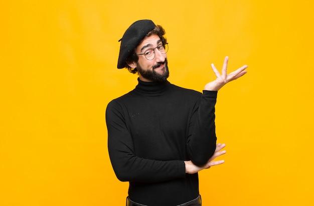 Молодой французский художник мужчина гордо и уверенно улыбается, чувствуя себя счастливым и довольным и показывая концепцию на копией пространства на оранжевой стене