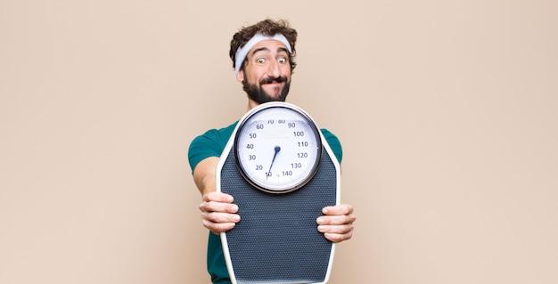 平らな壁に対して重量スケールを保持している若いスポーツ男