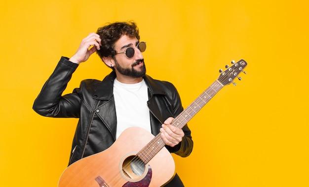 困惑と混乱、頭をかき、ギター、ロックンロールの概念と側にいる感じの若いミュージシャン男