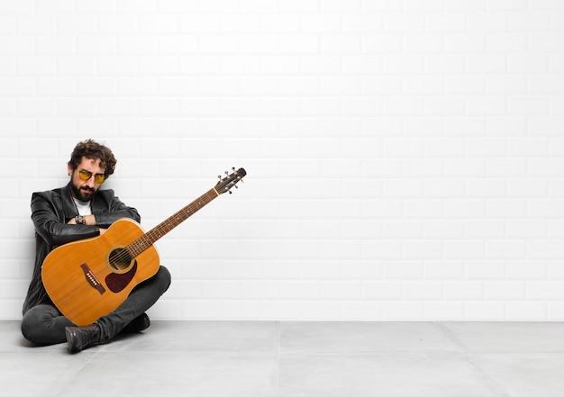 ギター、ロックンロールの概念と交差した腕に深刻なイライラし、怒っている、不満と失望を感じている若いミュージシャン男