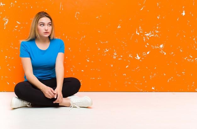 困惑して混乱している若いブロンドの女性、床に座って問題への答えを知らない、神経質なジェスチャーで唇をかむ