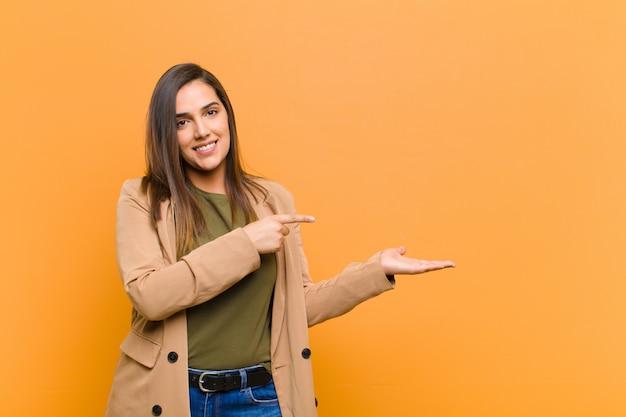 Молодая красивая женщина улыбается, чувствуя себя счастливым, беззаботным и довольным, указывая на концепцию или идею на копии пространства на стороне, изолированные против оранжевой стене