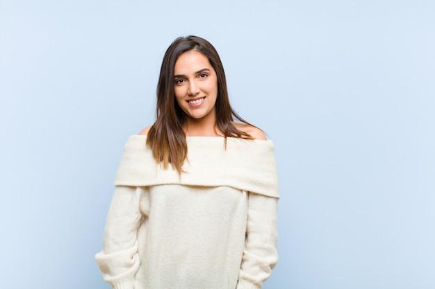 Молодая красивая женщина весело и небрежно улыбается с позитивным, счастливым, уверенным и расслабленным выражением на фоне голубой стены