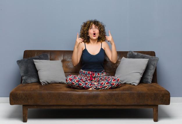 ソファに座ってスペースをコピーするために両手を上向きに見て、ショックを受け、驚いて、口を開けて見て若いきれいな女性。