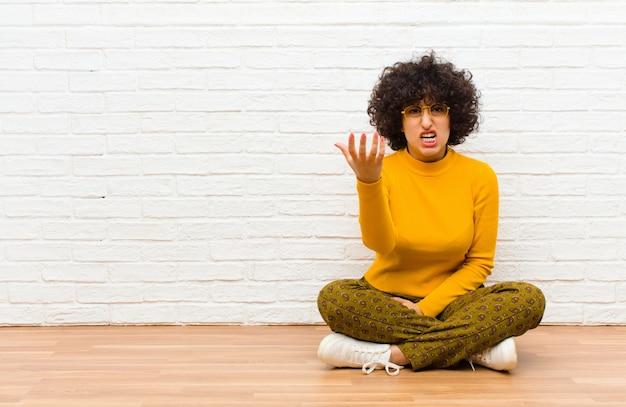 Молодая симпатичная афро женщина, выглядящая сердитой, раздраженной и разочарованной