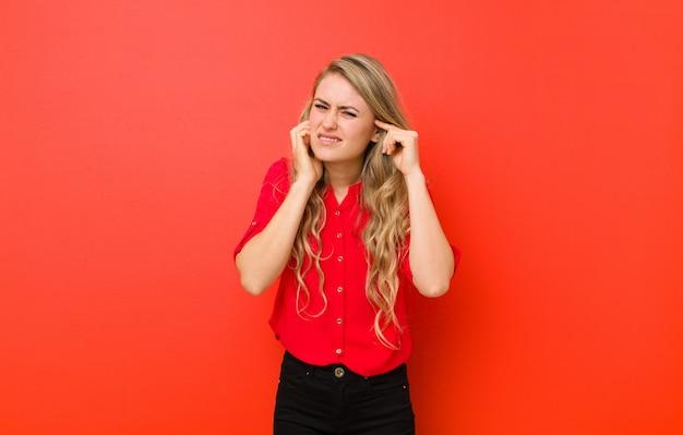 Молодая блондинка выглядит злой, напряженной и раздраженной, прикрывая оба уха оглушительным шумом, звуком или громкой музыкой на фоне красной стены