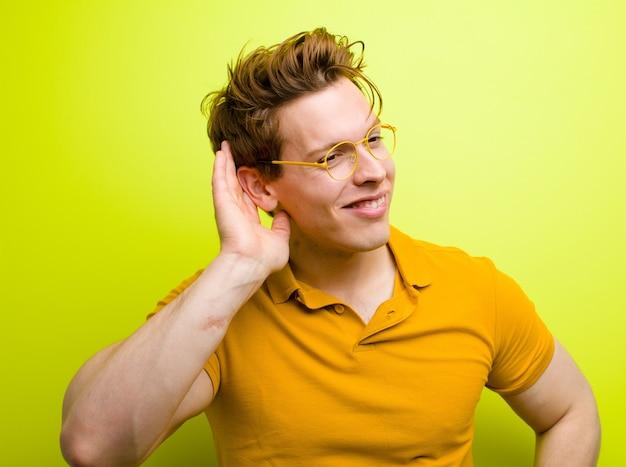 Молодой рыжеволосый мужчина улыбается, с любопытством смотрит в сторону, пытается выслушать сплетни или подслушать секрет у стены цвета