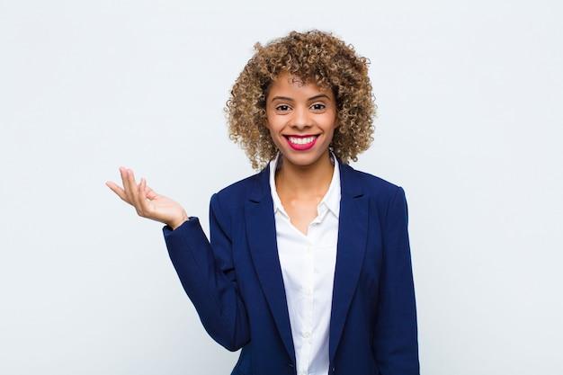 若い女性アフリカ系アメリカ人の幸せ、驚き、陽気、前向きな姿勢で笑顔、フラットの壁に対する解決策やアイデアを実現
