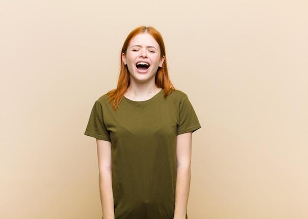 Молодая рыжеволосая красотка агрессивно кричит, выглядит очень злой, расстроенной, возмущенной или раздраженной, кричит нет