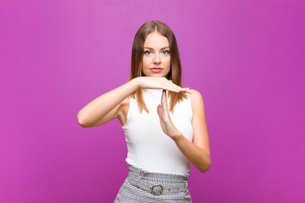 Красноволосая красотка выглядит серьезной, строгой, злой и недовольной, делая знак тайм-аут против фиолетовой стены