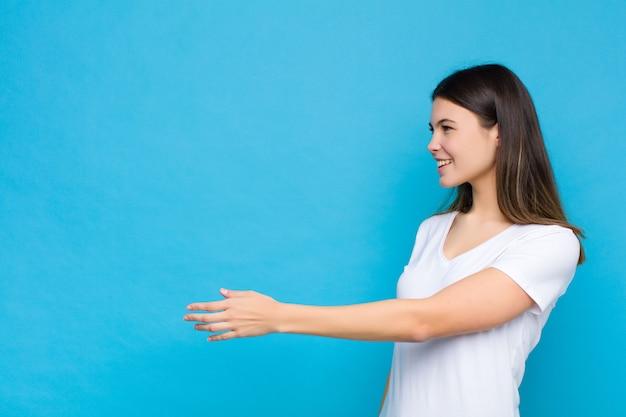 若いきれいな女性の笑みを浮かべて、あなたに挨拶し、成功した取引、青い壁に対する協力の概念を閉じるために手を振るを提供しています