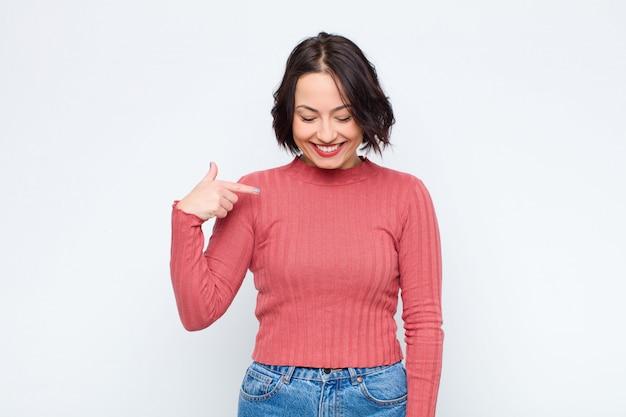 Молодая красивая женщина весело и небрежно улыбаясь, глядя вниз и указывая на грудь на белой стене