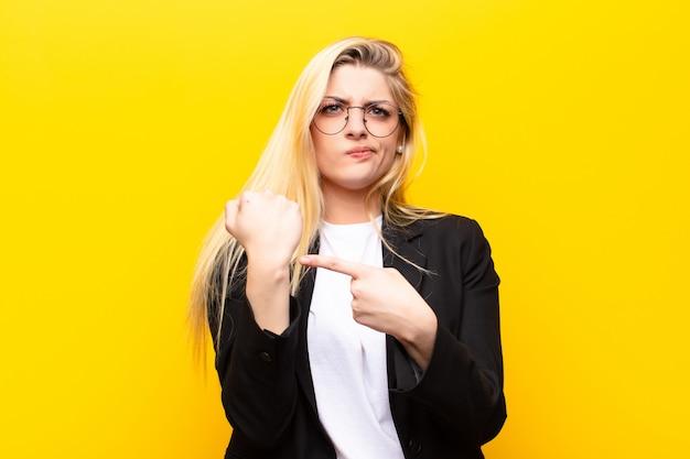 Молодая красивая белокурая женщина нетерпеливо и сердито, указывая на часы, просит пунктуальность, хочет быть вовремя у желтой стены