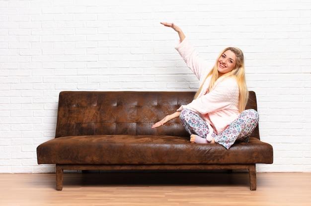Молодая красивая блондинка улыбается, чувствуя себя счастливым, позитивным и удовлетворенным, держа или показывая объект или концепцию на копией пространства