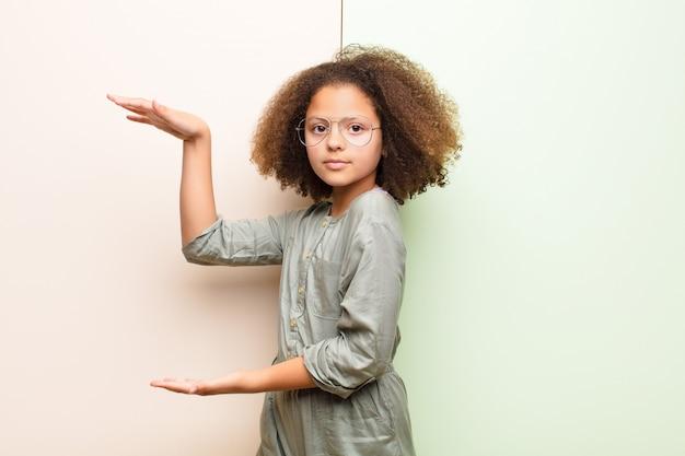 Афро-американская маленькая девочка держит объект обеими руками на боковой копией пространства, показывая, предлагая или рекламируя объект против плоской стены