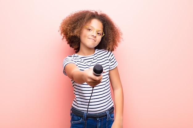 Афро-американская маленькая девочка против плоской стены с микрофоном