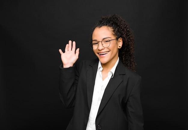 若い黒人女性の幸せと陽気な笑顔、手を振って、歓迎と挨拶、または黒い壁に別れを告げる