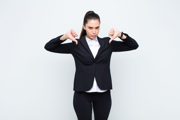 Молодая красивая женщина, глядя грустно, разочарован или злой, показывает палец вниз в разногласия, чувствуя разочарование бизнес-концепцию
