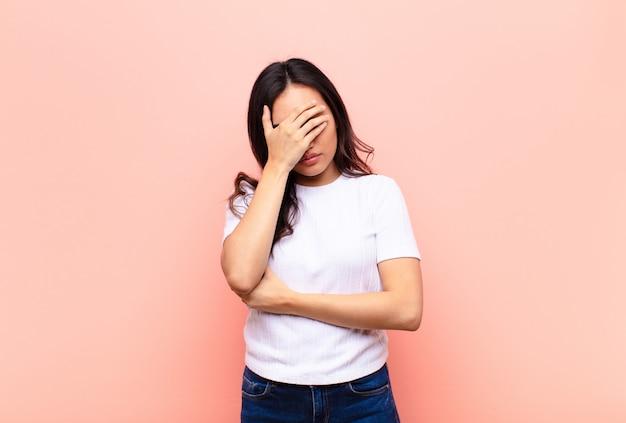 手で顔を覆っているストレス、恥ずかしい、または動揺、頭痛で探している若いラテンきれいな女性