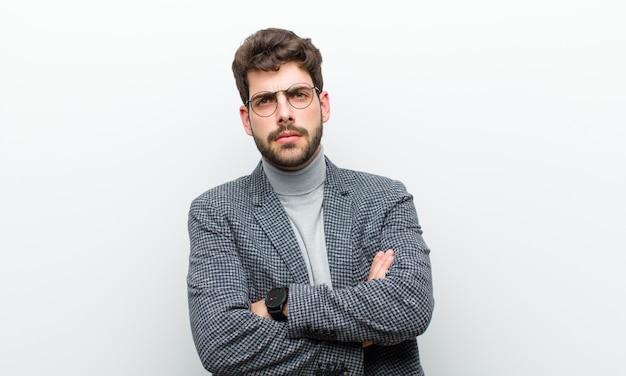 Молодой менеджер человек чувствует себя недовольным и разочарованным, выглядит серьезным, раздраженным и злым со скрещенными руками на белой стене