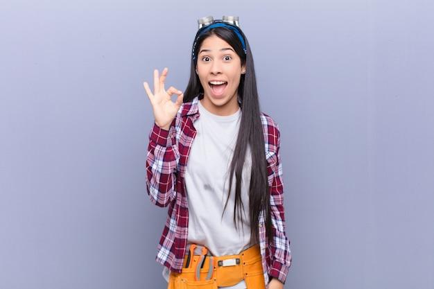 若いラテン女性成功と満足を感じて、口を大きく開けて笑って、手でいい兆候を作る