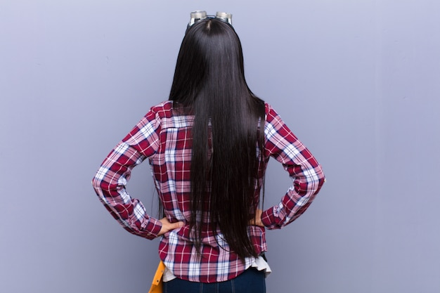 若いラテン女性の混乱や満腹感、疑問や質問、疑問に思う、腰に手を当てて、リアビュー