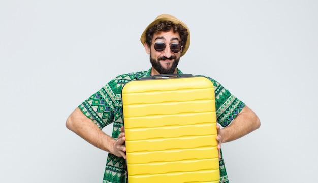 Молодой туристский человек с случаем костюма против белой стены. концепция путешествия