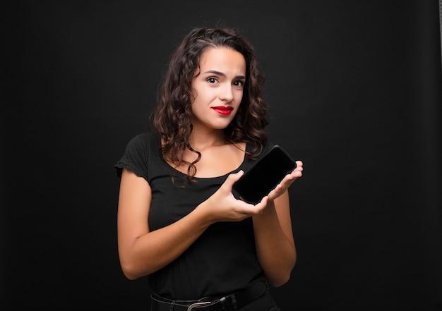 Молодая симпатичная женщина чувствует себя озадаченной и смущенной, с тупым, ошеломленным выражением лица, глядя на что-то неожиданное, держащее смартфон
