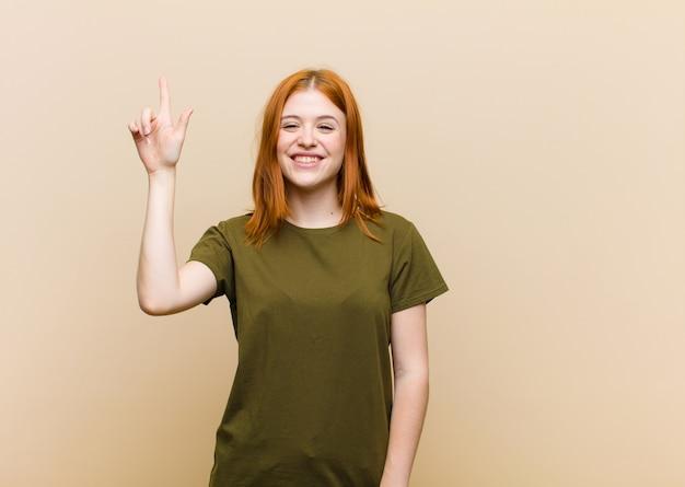 Молодая рыжая красотка улыбается весело и счастливо, указывая одной рукой вверх, чтобы скопировать пространство
