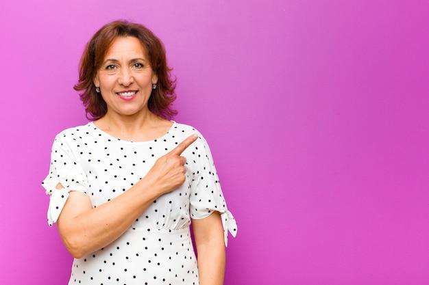 中年の女性、元気いっぱいに笑って、幸せと側と上を指して、紫色の壁にコピースペースでオブジェクトを示す