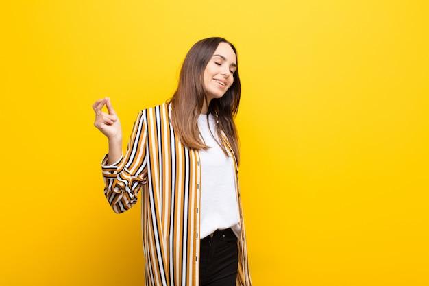 若いきれいな女性笑顔、屈託のない、リラックスして幸せな感じ、ダンス、音楽を聴いて、オレンジ色の壁のパーティーで楽しんで