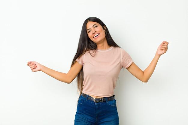 若い可愛いラテン女性笑顔、屈託のない、リラックスして幸せ、ダンスと音楽を聴いて、パーティーで楽しんで