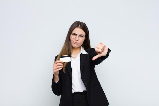 クロス、怒り、イライラ、失望または不満を感じて、クレジットカードで真剣な表情で親指を下に示す若いきれいな女性