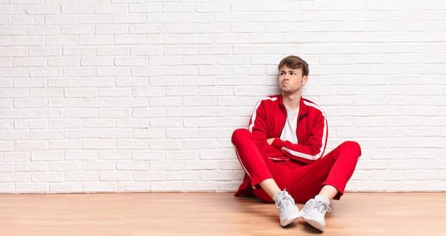 疑いや思考、唇をかむと不安と緊張を感じて、床に座っている側のスペースをコピーしようとしている若いブロンドの男