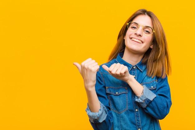 黄色の壁に対して幸せと満足を感じて、元気に、さりげなく側のコピースペースを指している若いきれいな女性