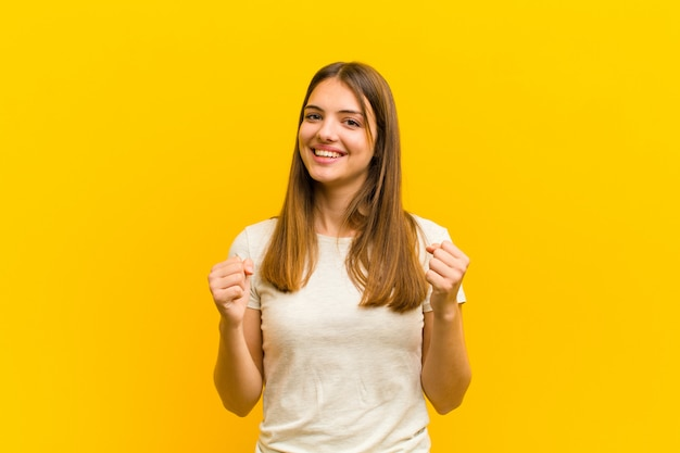 ショック、興奮、幸せ、笑いと成功を祝う若いきれいな女性、すごい!オレンジ色の壁に対して