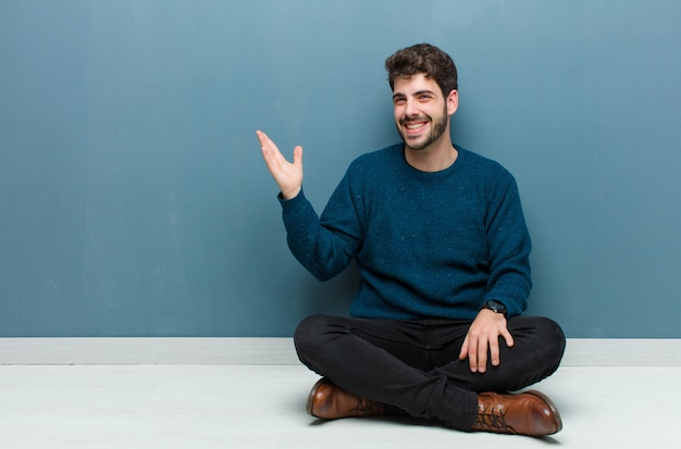 Молодой красавец сидит на полу, чувствуя себя счастливым, удивленным и веселым, улыбаясь позитивным настроем, понимая решение или идею
