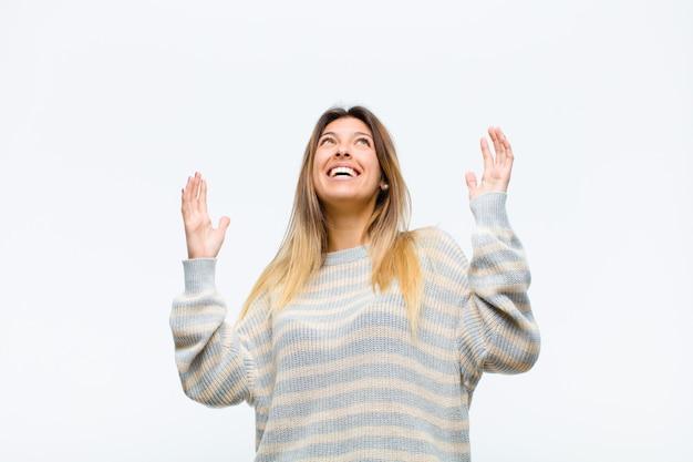 幸せ、驚き、幸運、驚きを感じている若いきれいな女性、白い壁に対して空中で両手で勝利を祝う