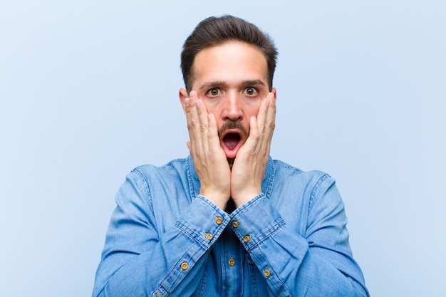 Молодой красивый мужчина, чувствуя себя шокированным и испуганным, выглядит испуганным с открытым ртом и руками на щеках
