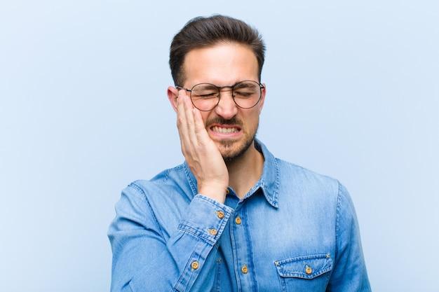 若いハンサムな男の頬を保持し、痛みを伴う歯痛に苦しんで、病気、悲惨、不幸を感じて、歯科医を探しています