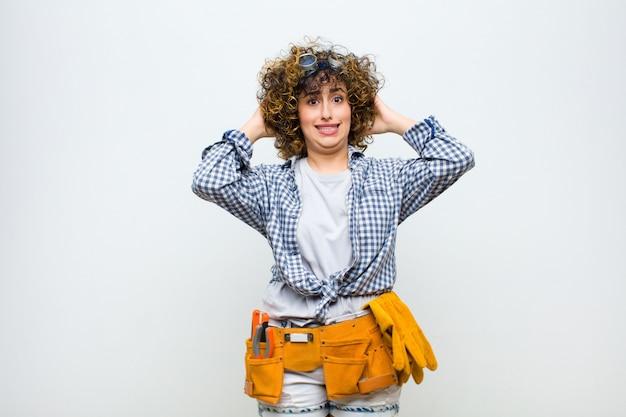 ストレス、心配、不安、怖い、頭に手を当てて、白い壁に対して誤ってパニックを感じる若い家政婦の女性