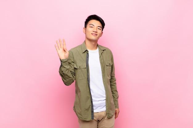 若い男が喜んで元気に笑って、手を振って、歓迎と挨拶、または色の壁に別れを告げる
