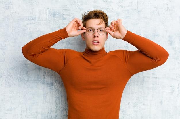 Молодой рыжеволосый мужчина, чувствуя себя шокированным, удивленным и удивленным, держит очки с удивленным, не верящим взглядом у гранжевой стены