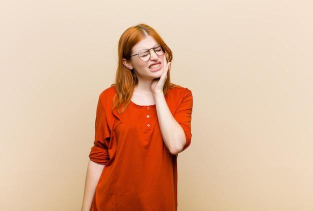 頬を押し、痛みを伴う歯痛に苦しんでいる若い赤毛のきれいな女性
