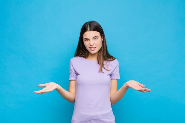 Молодая симпатичная женщина чувствует себя невежественной и растерянной, не уверенной, какой выбор или вариант выбрать, удивляясь голубой стене