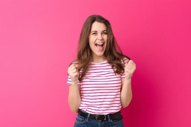 ショック、興奮、幸せ、笑いと成功を祝う若いきれいな女性、すごい!ピンクの壁に対して