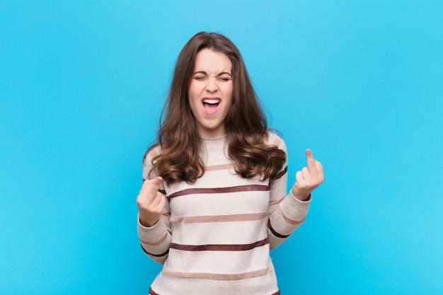 挑発的、攻撃的、わいせつな感じ、反抗的な態度で中指を弾く若いきれいな女性
