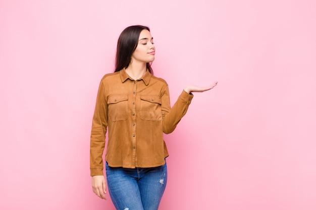 ピンクの壁の側に手で開催されたオブジェクトまたは概念を探して幸せとカジュアルな笑顔を感じて若いきれいな女性
